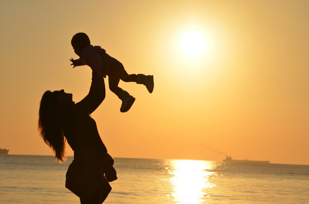 赤ちゃんを高く挙げている女性