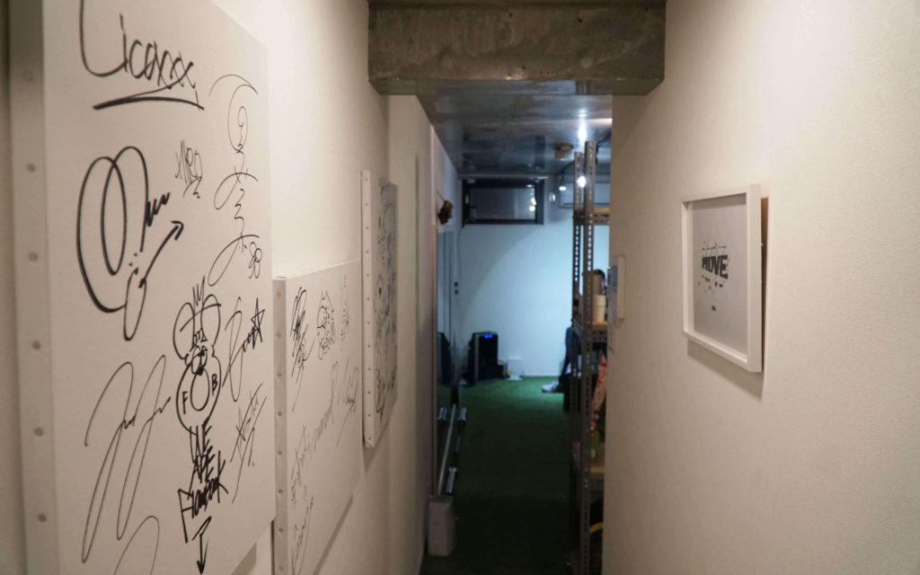 「studio kompas」のアーティストやタレントの数々のサインが並べられている通路